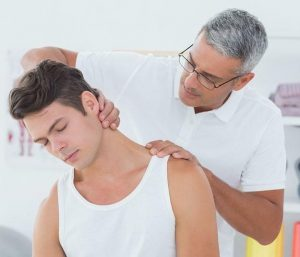 Man with shoulder pain and stiff neck sees chiropractor in knoxville for treatment