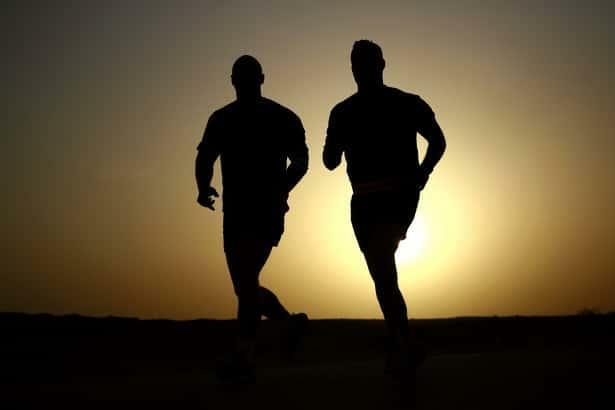 What causes shin splints with image of two runners at sunset