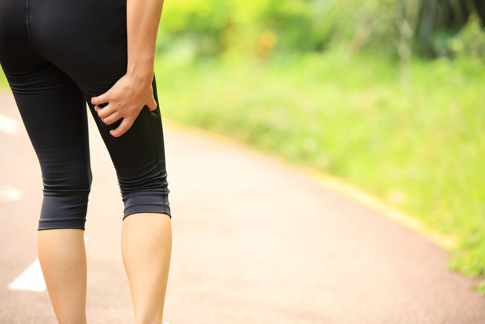 Woman walks with leg pain due to sciatic nerve issues in lower back