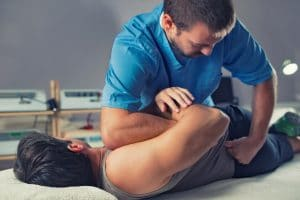 chiropractor adjusting a male patient lower back