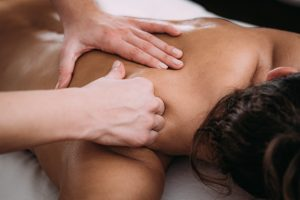 woman receiving a sports massage on her upper back