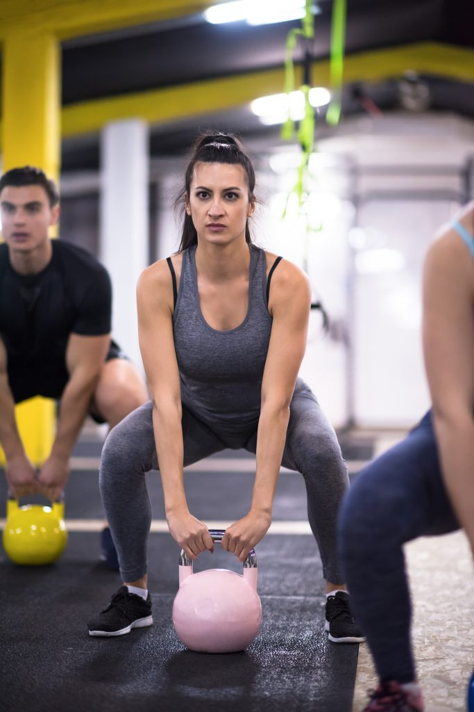 group of people working out and squatting with a kettle bell