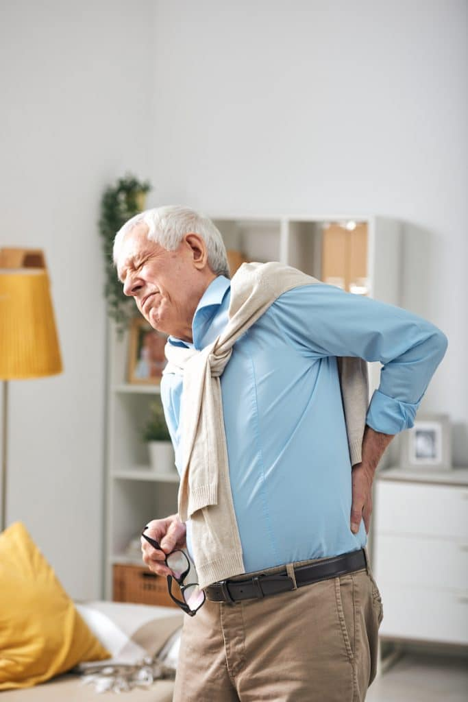 senior man holding his back due to pain