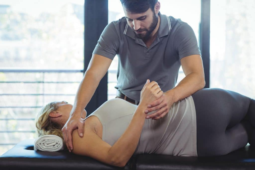 chiropractor adjusting female patients lower back