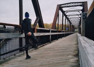 Runner stretching before a run on a bridge